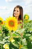 Mooi meisje onder de zonnebloemen Royalty-vrije Stock Fotografie