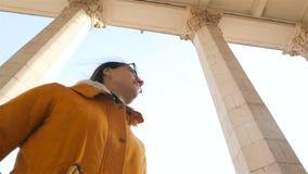 Mooi meisje op de achtergrond van hoge kolommen Langzame Motie stock videobeelden