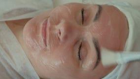 Mooi meisje op de procedure in de schoonheidssalon Verjonging en professionele huidzorg De schoonheidsspecialist past a toe stock video
