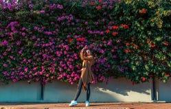 Mooi meisje op een achtergrond van een muur van bloeiende struiken stock afbeeldingen