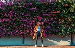 Mooi meisje op een achtergrond van een muur van bloeiende struiken royalty-vrije stock fotografie