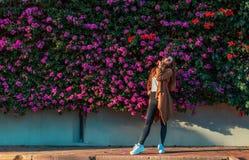 Mooi meisje op een achtergrond van een muur van bloeiende struiken stock foto