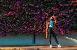 Mooi meisje op een achtergrond van een muur van bloeiende struiken stock afbeelding