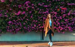 Mooi meisje op een achtergrond van een muur van bloeiende struiken royalty-vrije stock foto