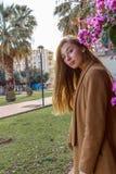 Mooi meisje op een achtergrond van een muur van bloeiende struiken royalty-vrije stock afbeelding