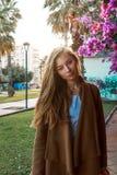 Mooi meisje op een achtergrond van een muur van bloeiende struiken stock fotografie