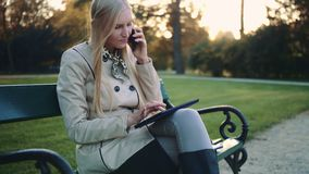 Mooi meisje op een bank met van tabletcomputer en cellphone zitting op parkbank stock videobeelden