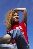 Mooi meisje op een blauwe hemelachtergrond Stock Afbeeldingen
