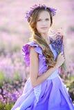 Mooi meisje op een gebied van lavendel op zonsondergang Stock Afbeelding