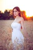 Mooi meisje op tarwegebied bij zonsondergang royalty-vrije stock afbeeldingen