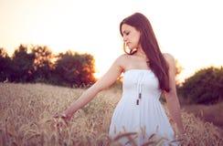Mooi meisje op tarwegebied bij zonsondergang royalty-vrije stock foto's