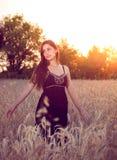 Mooi meisje op tarwegebied bij zonsondergang Stock Foto's