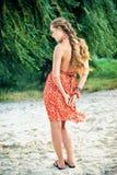 Mooi meisje in oranje kleding op strand Royalty-vrije Stock Foto