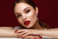 Mooi meisje in rode kleding met klassieke samenstelling en rode manicure Het Gezicht van de schoonheid royalty-vrije stock afbeeldingen