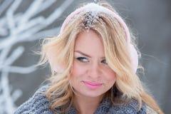 Mooi meisje in roze hoofdtelefoons op de sjaal met sneeuw stock fotografie
