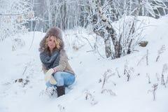 Mooi meisje in roze hoofdtelefoons op de sjaal met sneeuw stock foto's