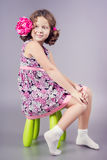 Mooi meisje in roze zitting op groene stoel Stock Afbeelding
