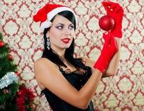 Mooi meisje in santahoed dichtbij een Kerstmisboom Stock Afbeeldingen