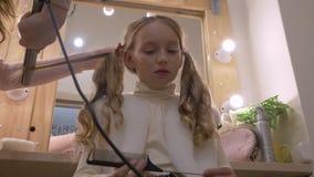 Mooi meisje terwijl het krullen van lang haar met haarijzer in herenkapper lage hoek stock footage