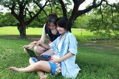 Mooi meisje twee op een laptop computer Stock Foto's