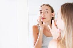 Mooi meisje, vrouw wat betreft haar neus terwijl het kijken in de spiegel, schoonheidsconcept, plastieken stock afbeeldingen