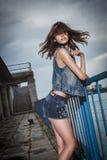 Mooi meisje in winderige voorwaarden op de dijk Stock Afbeelding