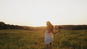 Mooi meisje in witte kleding die op plattelandsgebied lopen, die in een weide in zonstralen genieten van, het glimlachen stock footage