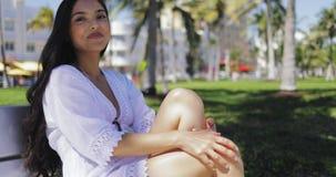 Mooi meisje in witte kleding op bank in park stock videobeelden
