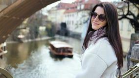 Mooi meisje in zonnebril genieten die op dijk in achtergrondveerboot op waterkanaal lopen stock videobeelden