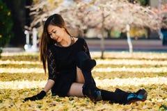 Mooi meisje in zwarte uitstekende kleding en handhandschoen De vrouw in het retro kleding spelen in het park met ginko doorblader stock foto
