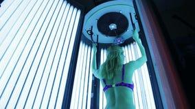 Mooi meisje in zwempak bij solarium stock video