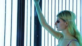 Mooi meisje in zwempak bij solarium stock footage