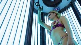 Mooi meisje in zwempak bij solarium stock videobeelden