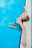 Mooi meisje in zwempak het ontspannen door de pool Royalty-vrije Stock Foto's