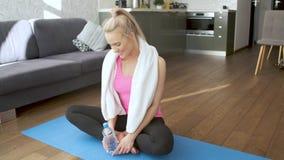 Mooi middenleeftijds blond vrouwelijk afvegend zweet met handdoek na fysieke training stock footage