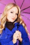 Mooi model in blauwe laag met een paraplu stock afbeeldingen