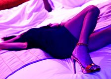 Mooi model in purpere ultraviolet licht schitterende benen in hoge hielen stock afbeeldingen