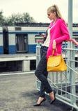 Mooi modern meisje met een mobiele telefoon op het platform Stock Afbeelding