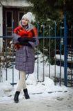 Mooi modieus blondemeisje die in pom pom hoed met wijn rode lippen en heldere sjaal in de stad lopen stock afbeeldingen