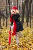 Mooi modieus jong meisje met rode paraplu, rood GLB en rode sjaal in het park Stock Foto