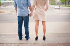 Mooi modieus jong paar die en handen op een achtergrond van een grote stad bevinden zich houden, liefde, het dateren, Romaanse le Royalty-vrije Stock Foto's
