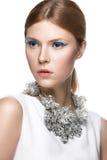 Mooi modieus meisje met de blauwe pijlen op ogen, vlot haar en originele decoratie rond haar hals Model in wit beau Royalty-vrije Stock Fotografie