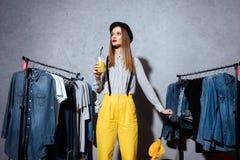 mooi modieus meisje met jus d'orange en paraplu die zich in boutique bevinden royalty-vrije stock fotografie