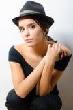 Mooi modieus meisje in zwarte kleren en zwarte hoed agains stock foto