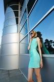 Mooi modieus stedelijk meisje die zich voor de moderne bouw bevinden Royalty-vrije Stock Afbeeldingen