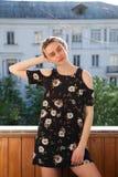 Mooi modieus vrouwenblonde in kleding met bloemen op de straat royalty-vrije stock foto