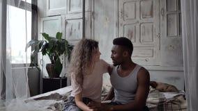 Mooi multi-etnisch paar die in pyjama's bij bed en het spreken zitten De man en de vrouw hebben een gesprek Langzame Motie stock footage