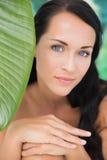 Mooi naakt brunette die bij camera met groen blad glimlachen Stock Afbeelding