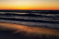 Mooi oceaan en zandstrand tijdens zonsondergang royalty-vrije stock afbeeldingen