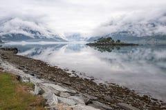 Mooi ochtendlandschap op fjord met kruipende wolken Rotsachtig eiland met bomen en prachtige bezinning in het water, Noorwegen Stock Afbeelding